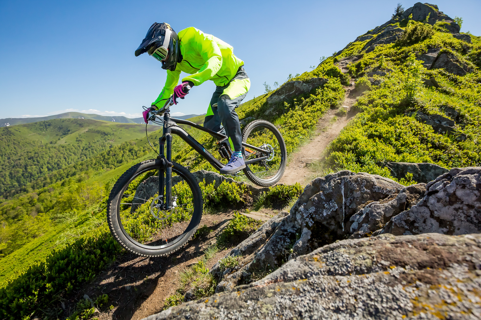 Professional athlete is riding enduro bicycle on a beautiful rocky trail.